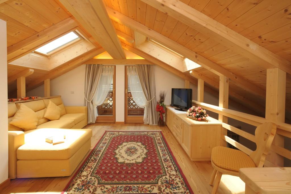 salotto con divano chiaro tappeto rosso e mobili in legno